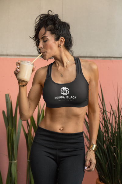 fit woman drinking a healthy beverage in a sports bra